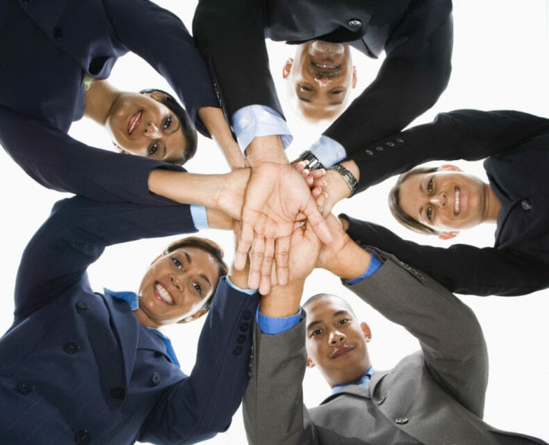 Cheesy stock photo showing businesspeople in a hands-in huddle.